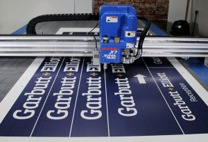 Signage being knife cut on a DYSS - Sign and Display Production Systems